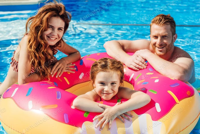 happy young parents with daughter floating in rubber ring looking at camera at swimming pool