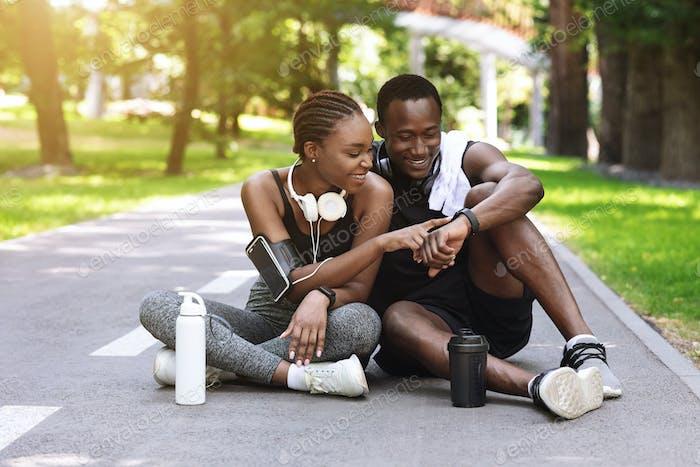Joyful black couple resting after jogging in park, checking smartwatch
