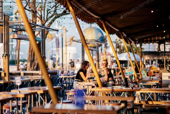 Vacay Mode. Girls sitting at riverside restaurant near Chao phraya river during sunset in the city