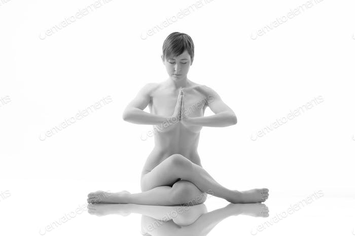 Young naked woman meditating in a yoga pose