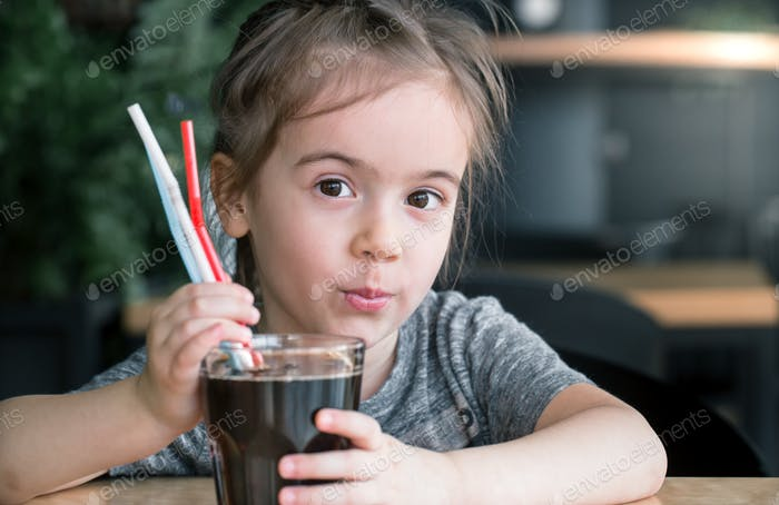 un niño bebe una bebida de una paja