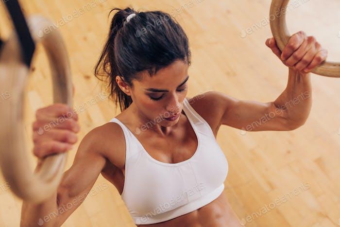 Starke Frau tun Klimmzüge mit Gymnastikringen im Fitnessstudio