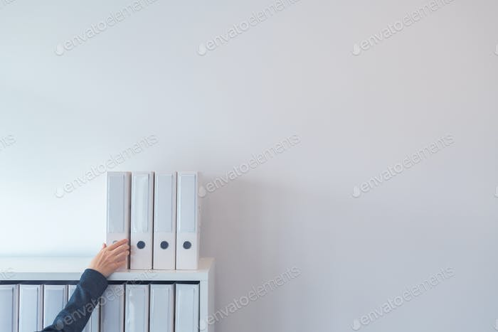 Hand reaching for document ring binder on office shelf