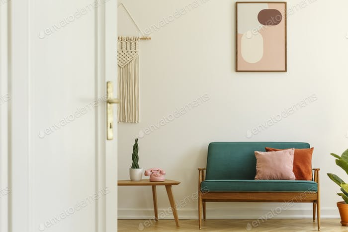 Poster above green couch with pillows in living room interior wi