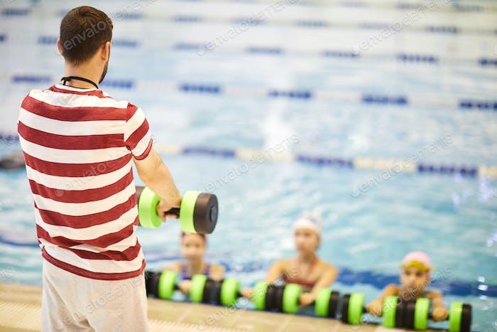 Instructor conducts classes in aqua aerobic