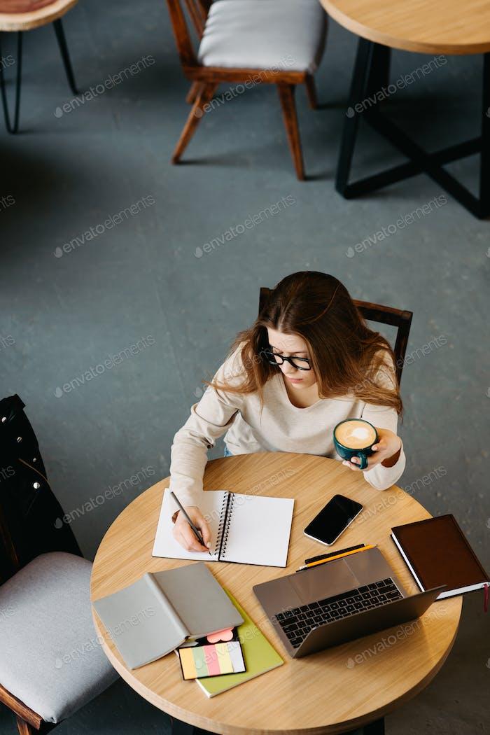 Freiberufliche Frau mit Brille arbeiten am Laptop und macht Notizen