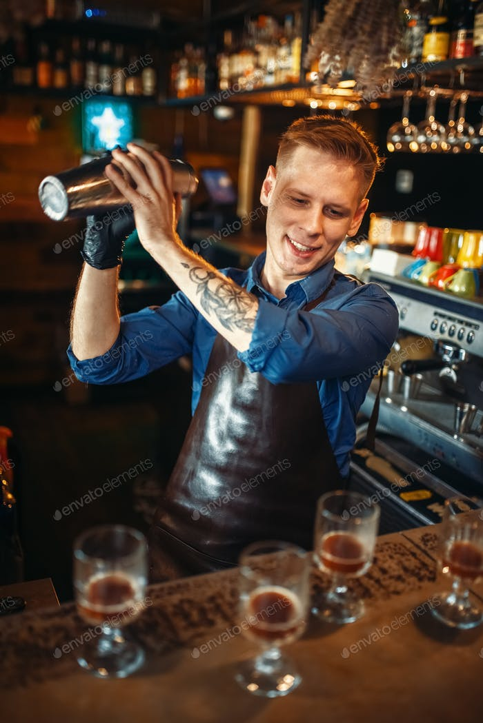 Bartender works with shaker at the bar counter