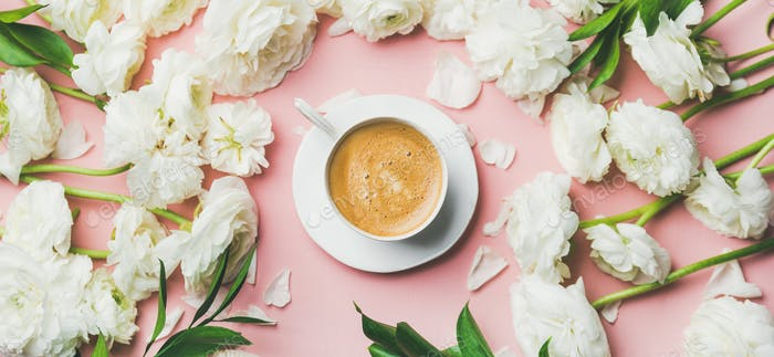 Cup of coffee and white ranunculus flowers on pink background