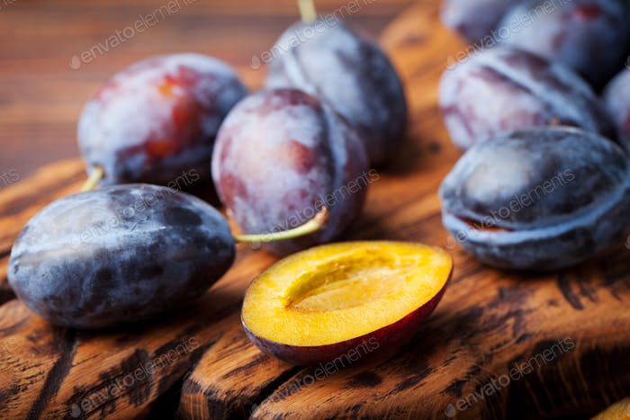 Fresh organic plums on rustic wooden cutting board