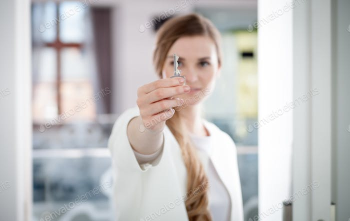 Happy woman holding house key of her new aparment