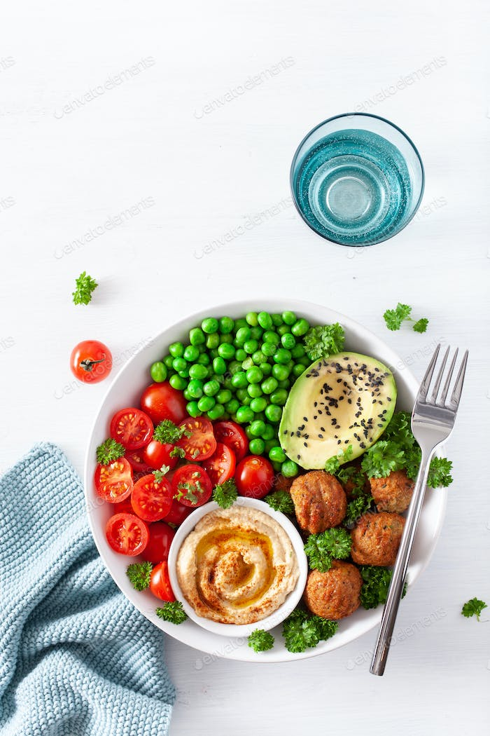 healthy vegan lunch bowl with falafel hummus tomato avocado peas