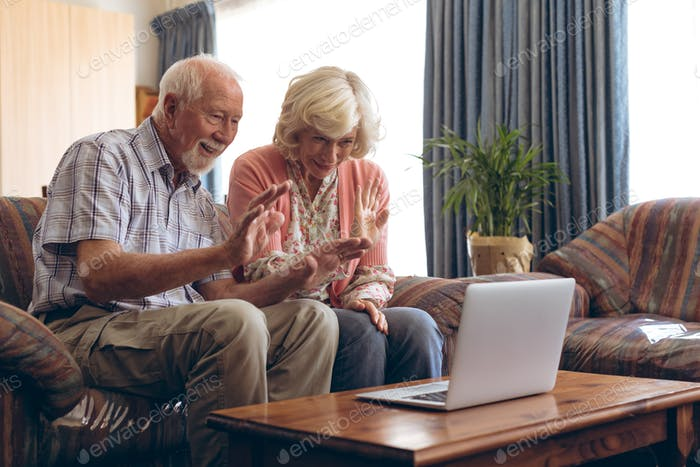 Happy senior couple making video call on laptop at retirement home