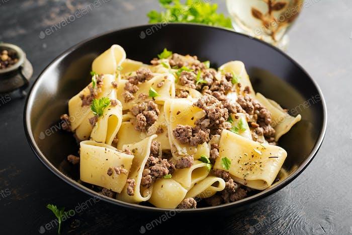 Pasta Calamarata mit Hackfleisch in schwarzer Schüssel. Italienische Küche.
