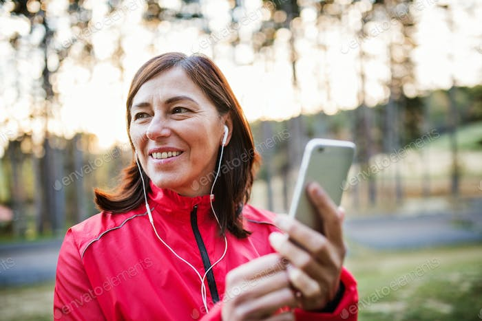 A female runner with earphones outdoors in autumn nature, using smartphone.