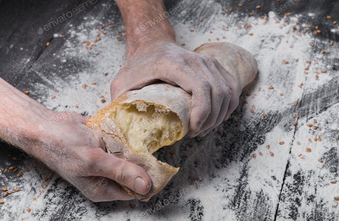 Bakery concept background. Hands breaking bread loaf
