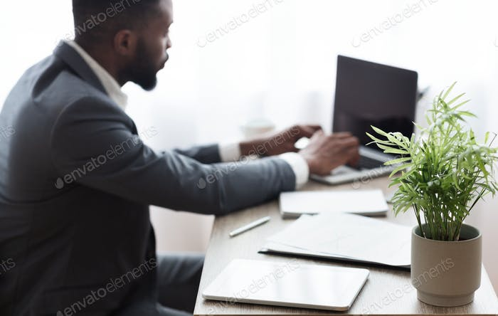 Business background. Businessman working on laptop in modern office