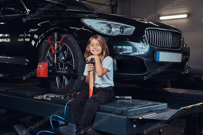 Little child and shiny car at auto service