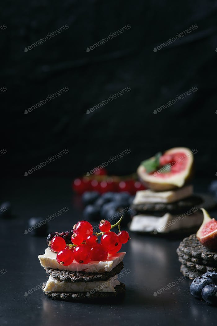 Black crackers with cheese and berries