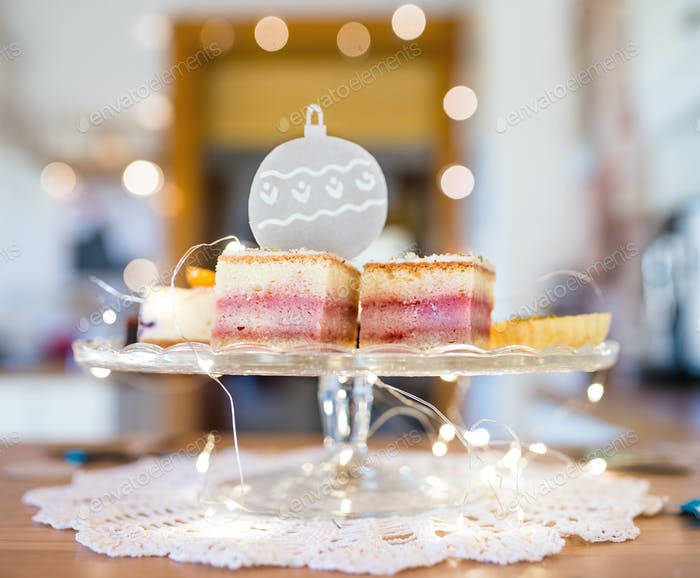 Selection of delicious cake desserts on tray, Christmas lights decorations.