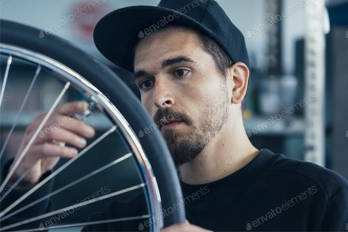 Close-up of worker checking bicycle wheel