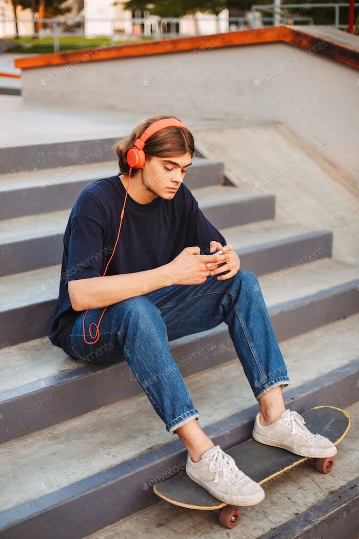 Young skater in orange headphones thoughtfully using cellphone s