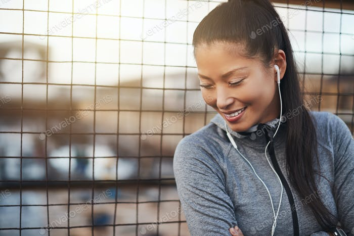 Asian woman smiling and listening to music before exercising outside