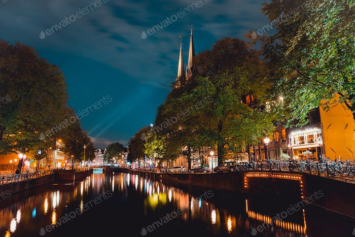 Night shot of Amsterdam canal with illuminated steeples of the church De Krijtberg in downtown