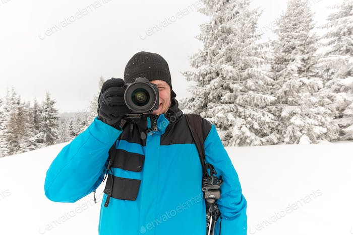 Male traveler with backpack takes pictures