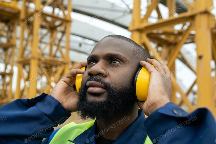 Construction worker in protective headphones