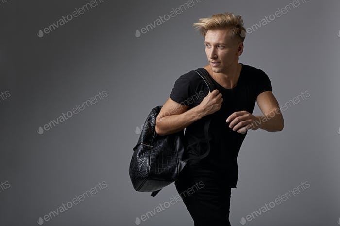 Handsome young man running with a backpack on shoulders