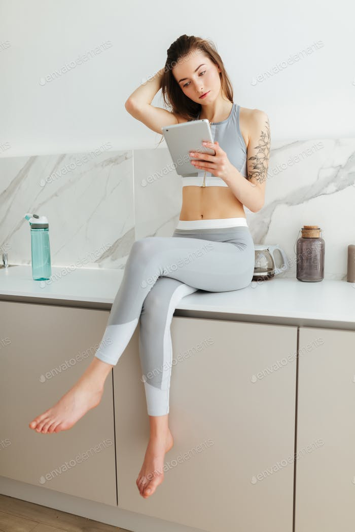 Girl in sporty top and leggings sitting on kitchen table with laptop thoughtfully looking aside