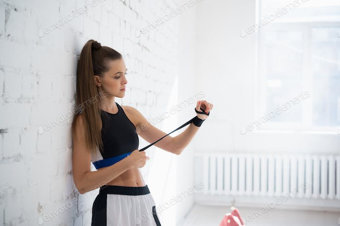 A young strong girl mixed martial arts fighter is preparing for sparring
