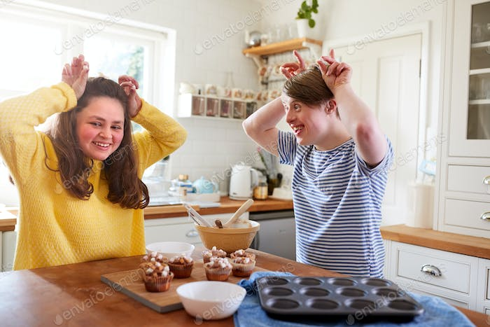 Young Downs Syndrome Couple Decorating Homemade Cupcakes With Marshmallows In Kitchen At Home