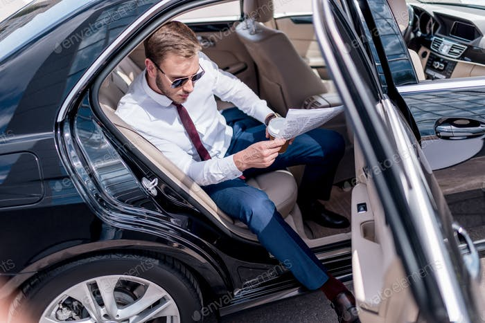 young stylish businessman in sunglasses with coffee and newspaper on backseat of car