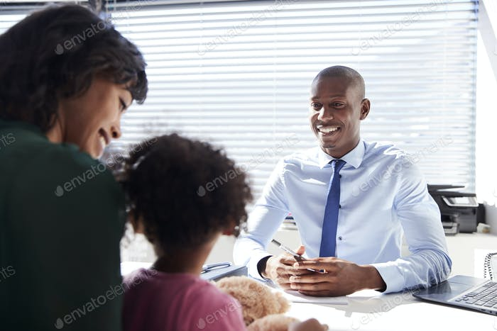 Mother And Daughter In Consultation With Doctor In Office