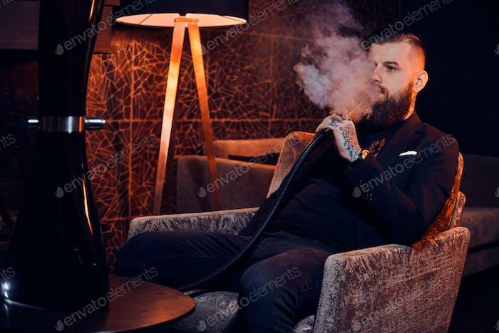 Nachdenklich tätowierter Mann sitzt auf dem Sessel und starten Rauch Shisha