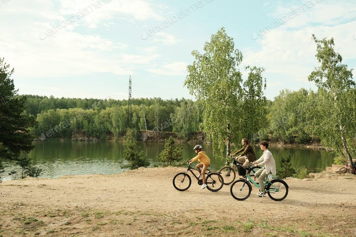 Side view of young family sitting on bicycles and moving along riverbank