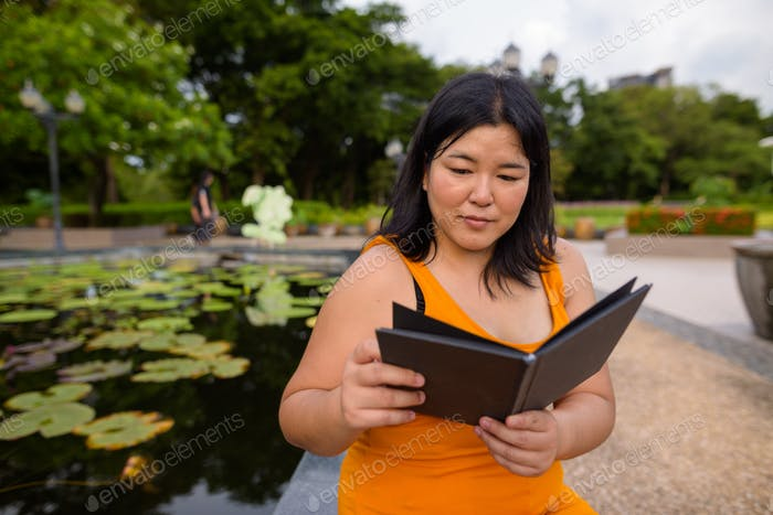Beautiful overweight Asian woman reading book in park