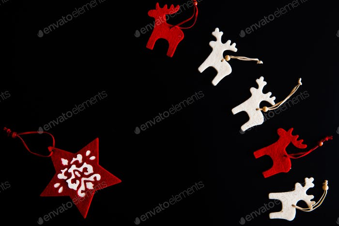 Red and white felt rein deers and snowflake isolated on black. Christmas background