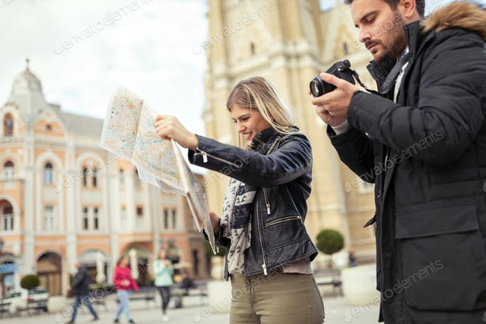 Young attractive happy couple enjoying city as tourists