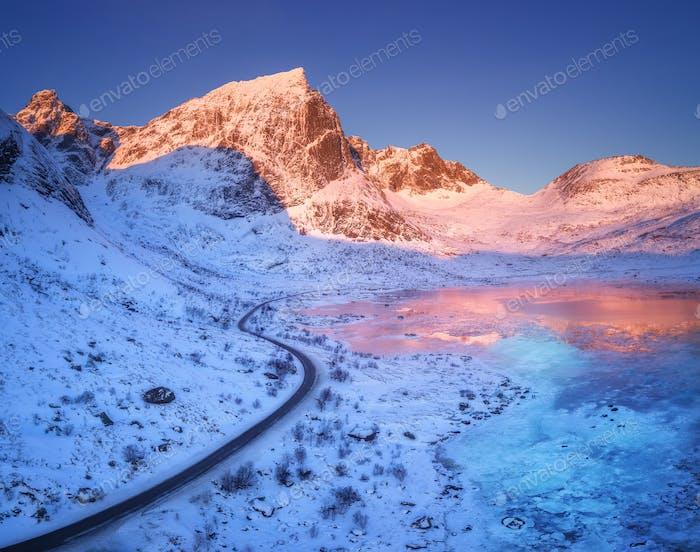 Luftbild der kurvenigen Straße, schneebedeckte Berge und blauer Himmel