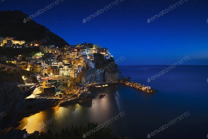 Manarola night. Village, rocks and sea. Cinque Terre, Italy