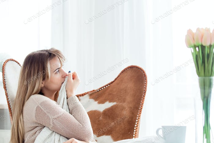 Young woman sitting on armchair at home thinking about something, positive emotions