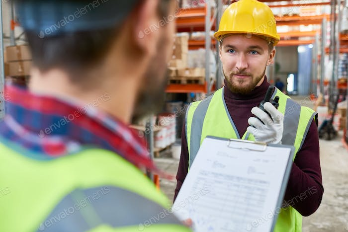 Young Worker Talking to Supervisor in  Warehouse
