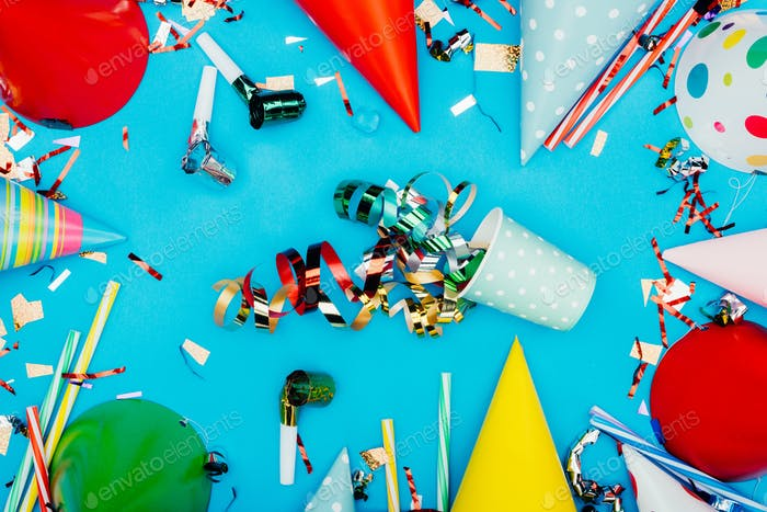 top view of confetti spilled from paper cup surrounded with holiday decor