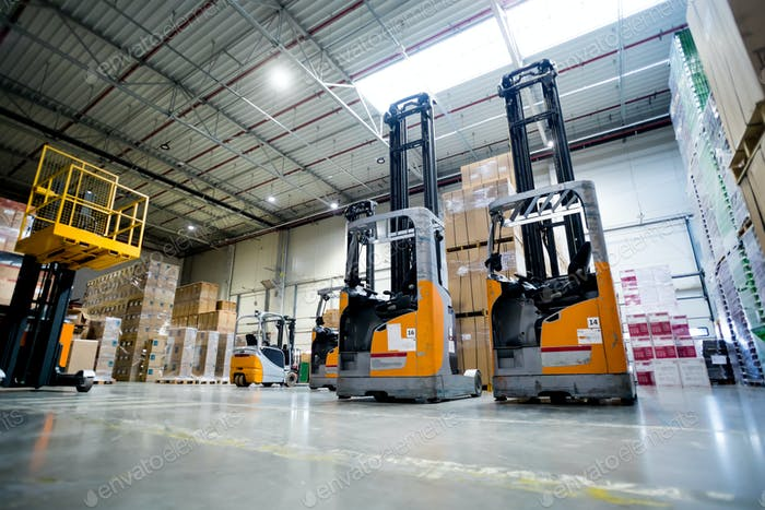 Two lift trucks parked on alley in huge warehouse