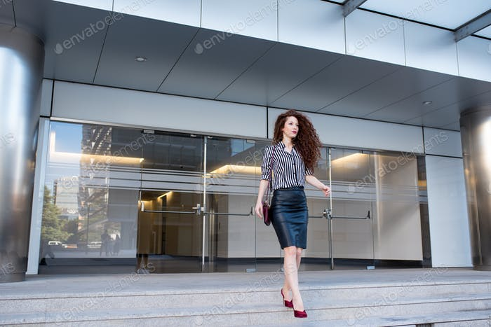 Young redhead business woman walking on the stairs