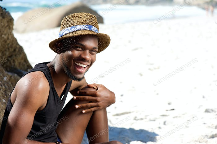 Happy guy sitting at the beach with hat