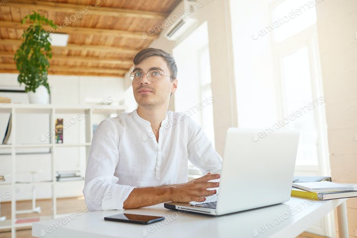 handsome pensive young businessman wears white shirt and spectacles using laptop