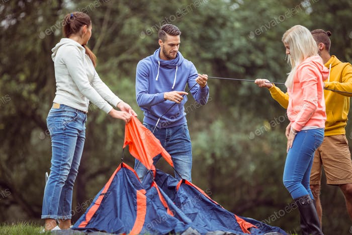 Happy friends setting up their tent in the countryside